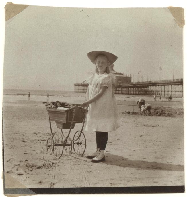 een-meisje-met-poppenwagen-op-het-strand-op-de-achtergrond-het-wandelhoofd-wilhelmina.-foto-ca-1905-onbekende-fotograaf.-collectie-hga-72dpi.jpg